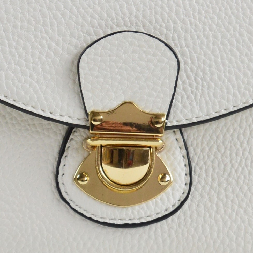 Gold plated handbag buckle on a white leather handbag